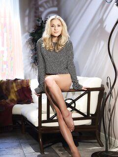 Красивая блондинка позирует голая на диване - фото