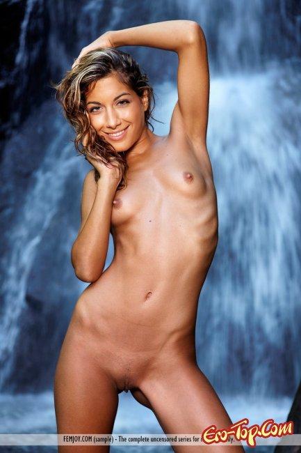 Девица у водопада с мокрой упругой попой позирует нагишом - фото.