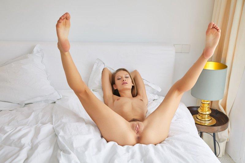 Сексуальная девушка позируя раздвигает ноги на кровати - фото