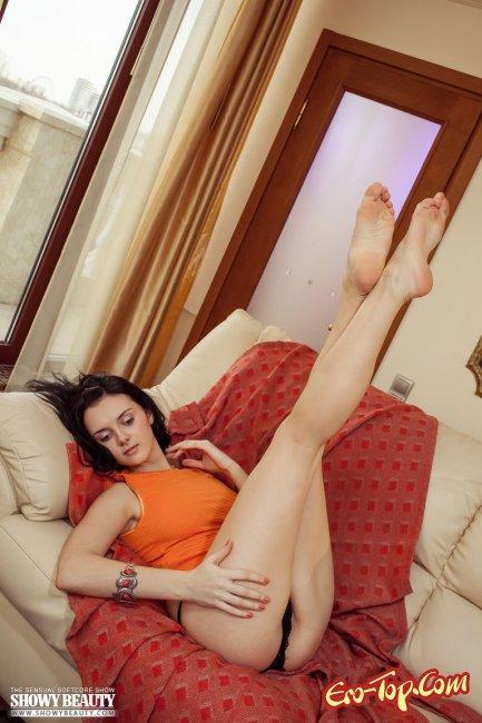 Страстная и обнаженная на диване соблазнительно шалит - фото эротика.