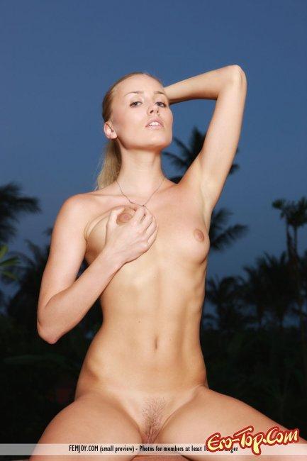Белокурая деваха под пальмами демонстрирует молодое тело - фото.