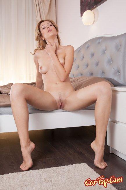 Прелестная модель позирует на кровати и светит гладкой щелкой - фото.