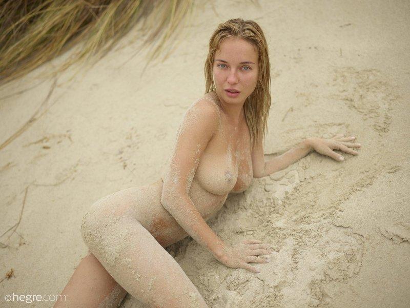 Голая красотка измазанная в песке позирует на пляже - фото