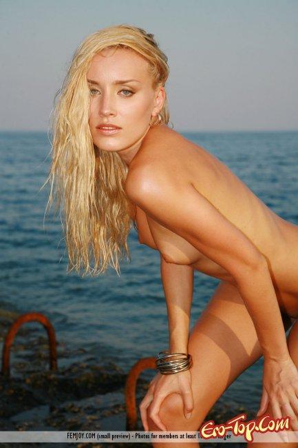 Голенькая на берегу моря принимает откровенные позиции - фото.