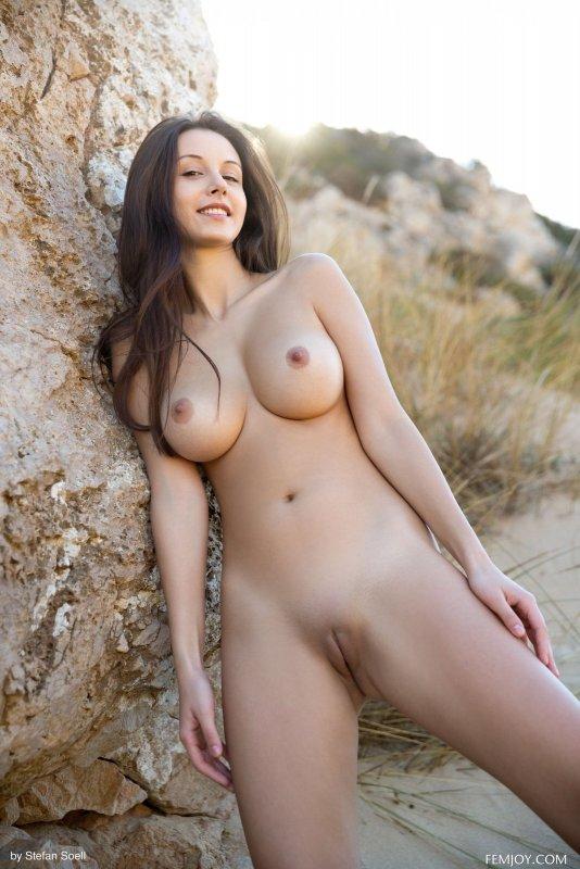 Голая девушка с крупными дойками позирует на природе - фото