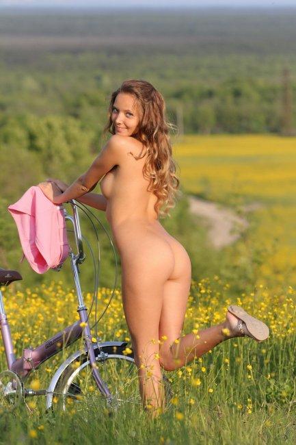 Голая девка на велосипеде позирует в поле - фото эротика.