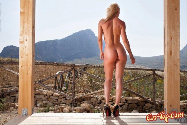 Шикарная голая блондинка на природе красиво позирует - фото эротика.