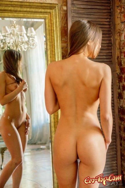 Стройная голая девушка перед зеркалом эротично позирует - фото.